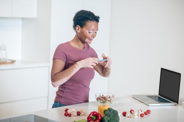 Imagen para publicar. una mujer de piel oscura haciendo una foto de una ensalada.