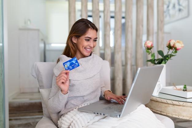 Imagen que muestra a la mujer bonita que hace compras en línea con tarjeta de crédito. mujer con tarjeta de crédito y usando laptop. concepto de compra en línea