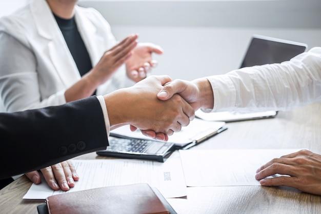 Imagen de un reclutador en traje y un nuevo empleado dándose la mano y aplaudiendo después de una buena entrevista.