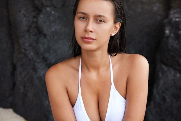 Imagen recortada de bonita mujer caucásica con cabello mojado, tiene pecho perfecto