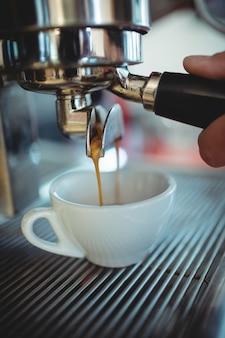 Imagen recortada de camarero con mango de máquina en café