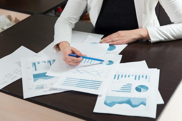 Imagen recortada de colegas de negocios que discuten los aspectos financieros de la empresa en primer plano.
