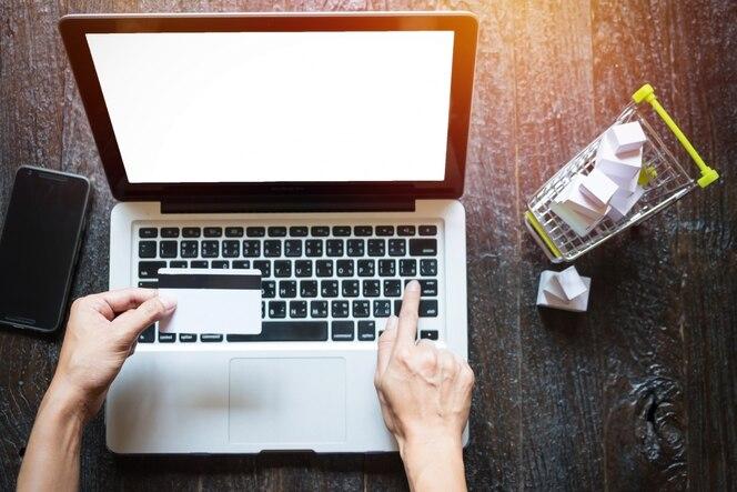 Imagen recortada de la mujer de la información de la tarjeta de crédito de entrada y clave en el teléfono o portátil mientras compra concepto en línea