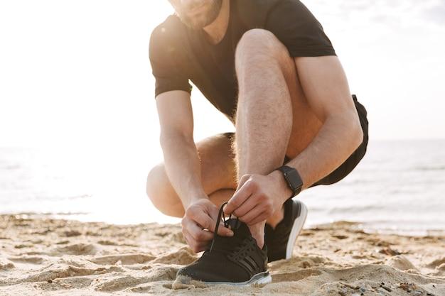 Imagen recortada de un deportista atarse los cordones de los zapatos