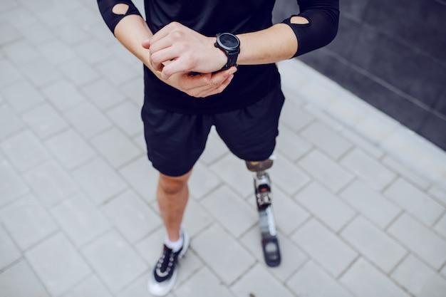 Imagen recortada de deportista caucásico con pierna artificial mirando el reloj de pulsera.