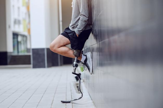Imagen recortada de deportista con pierna artificial de pie contra la pared y tomados de la mano en los bolsillos.
