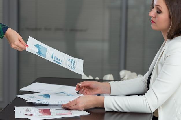 Imagen recortada de empresaria dando tabla de progreso a un colega en el escritorio en la oficina.