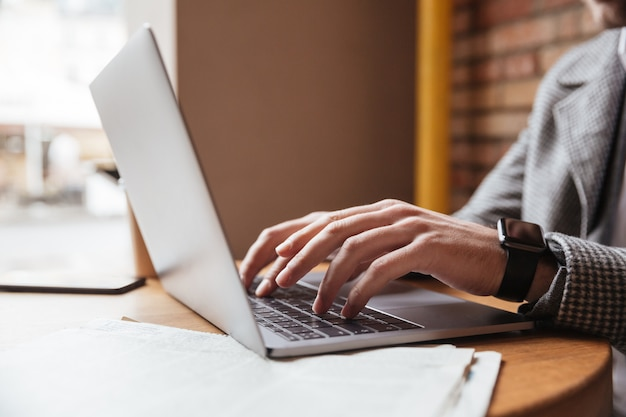 Imagen recortada del empresario en anteojos sentado junto a la mesa en la cafetería y usando la computadora portátil