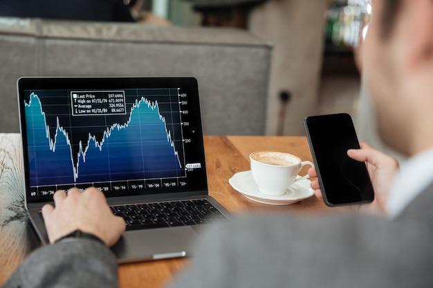 Imagen recortada del empresario sentado junto a la mesa en la cafetería y analizar indicadores en la computadora portátil mientras usa el teléfono inteligente