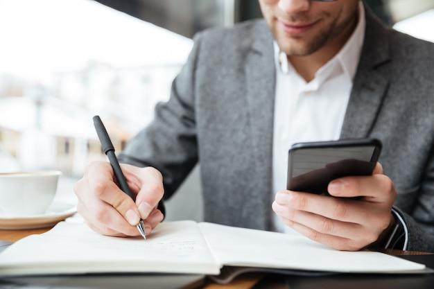 Imagen recortada del empresario tranquilo sentado junto a la mesa en la cafetería mientras usa el teléfono inteligente y escribe algo