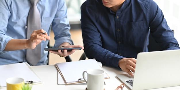 Imagen recortada del equipo de desarrolladores de negocios que trabaja junto con la computadora portátil y la tableta mientras está sentado en el escritorio de trabajo blanco que está rodeado por el portapapeles y la taza de café, concepto de colaboración.