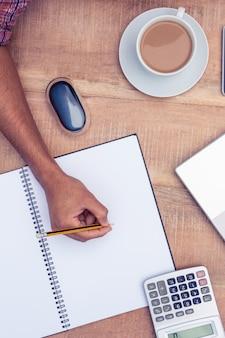 Imagen recortada de la escritura del hombre de negocios en el cuaderno en el escritorio en la oficina
