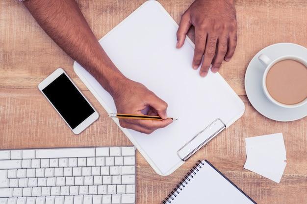 Imagen recortada de la escritura del hombre de negocios en el cuaderno por el teclado de computadora en el escritorio en la oficina