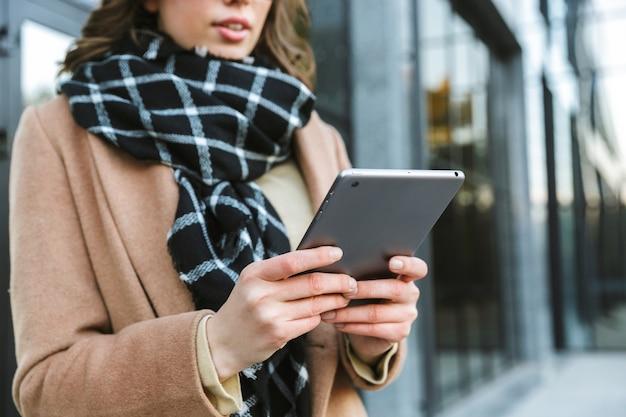 Imagen recortada de una hermosa joven al aire libre caminando por la calle con tablet pc.