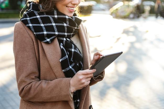 Imagen recortada de una hermosa joven feliz al aire libre caminando por la calle con tablet pc.