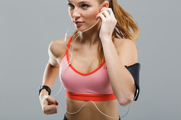Imagen recortada de hermosa mujer joven deportiva corriendo