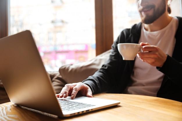 Imagen recortada del hombre barbudo usando laptop en café
