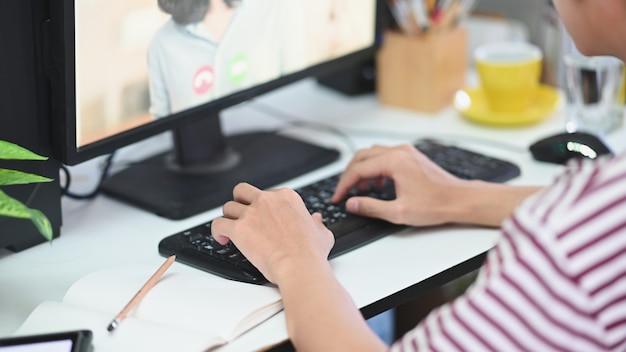 La imagen recortada del hombre está escribiendo en un teclado mientras realiza una videoconferencia en el escritorio de trabajo.