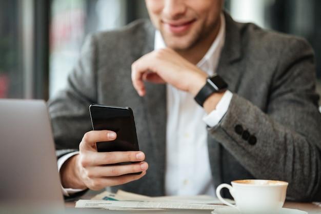 Imagen recortada del hombre de negocios feliz sentado junto a la mesa en la cafetería y usando el teléfono inteligente