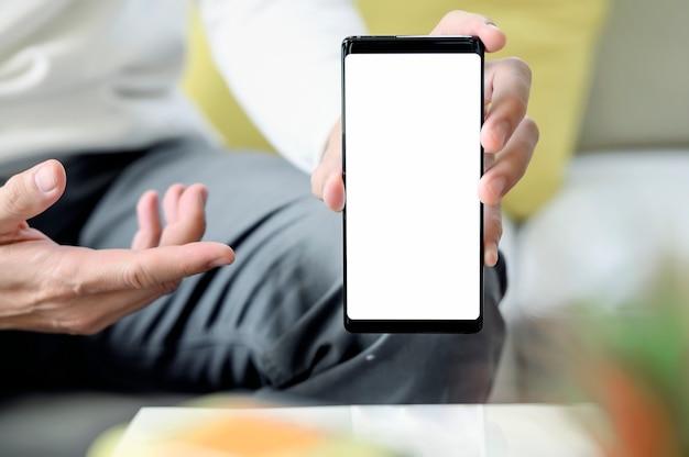 Imagen recortada del hombre sosteniendo y mostrando la pantalla en blanco del teléfono inteligente mientras está sentado en casa