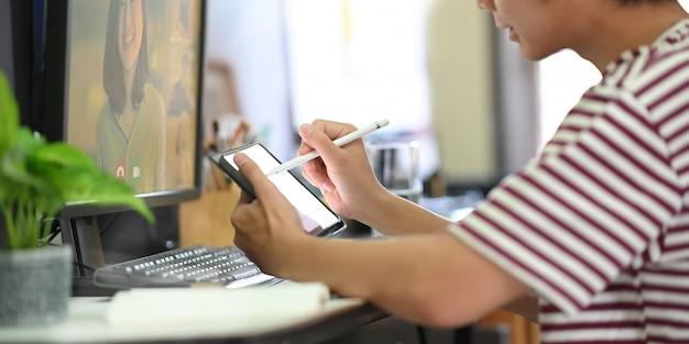 La imagen recortada del hombre está usando una tableta de computadora mientras realiza una video conferencia en el escritorio de trabajo.