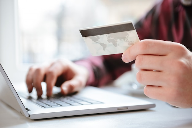 Imagen recortada de increíble joven con tarjeta de débito.