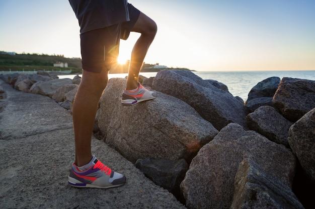 Imagen recortada de un joven deportista piernas en zapatillas de deporte