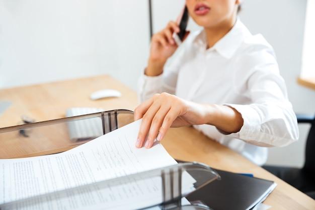 Imagen recortada de joven empresaria hablando por teléfono y tomando documentos de la mesa de la oficina