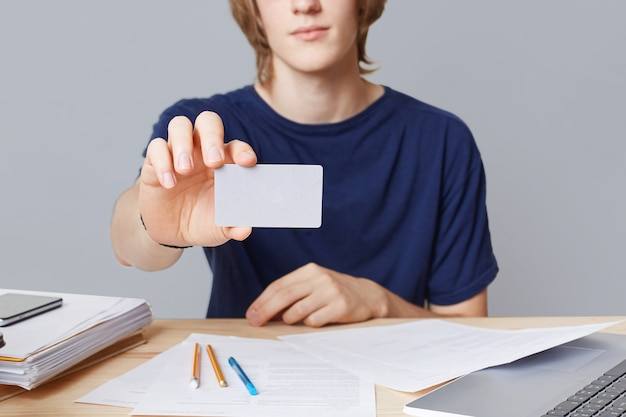 Imagen recortada de un joven empresario masculino vestido informalmente con una tarjeta con espacio de copia en blanco, se sienta en la mesa de trabajo, rodeado de papeles, aislado sobre la pared gris. empresario tiene tarjeta de visita