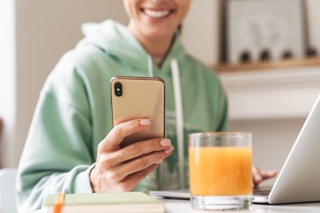 Imagen recortada de una joven mujer morena sonriente en el interior de su casa usando una computadora portátil y un teléfono móvil.