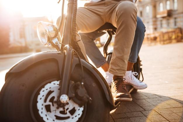 Imagen recortada de una joven pareja africana monta en moto moderna en la calle
