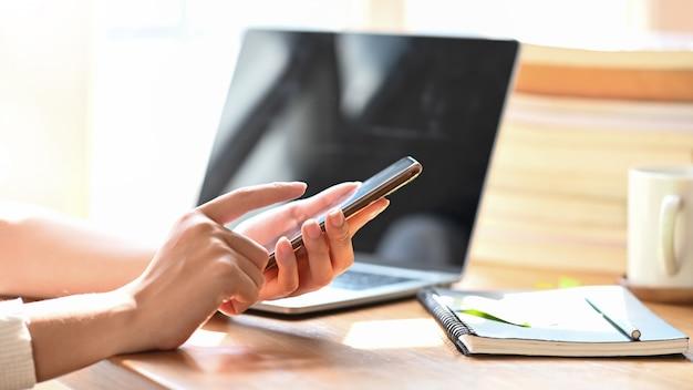 Imagen recortada de las manos de la mujer con smartphone en el escritorio de madera.