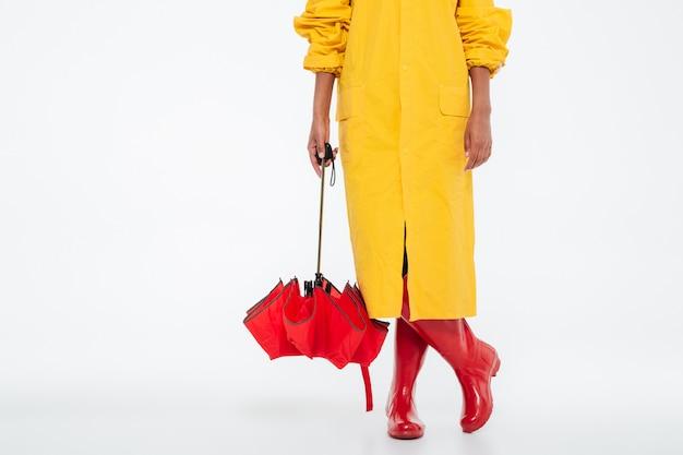 Imagen recortada de mujer africana en gabardina con paraguas