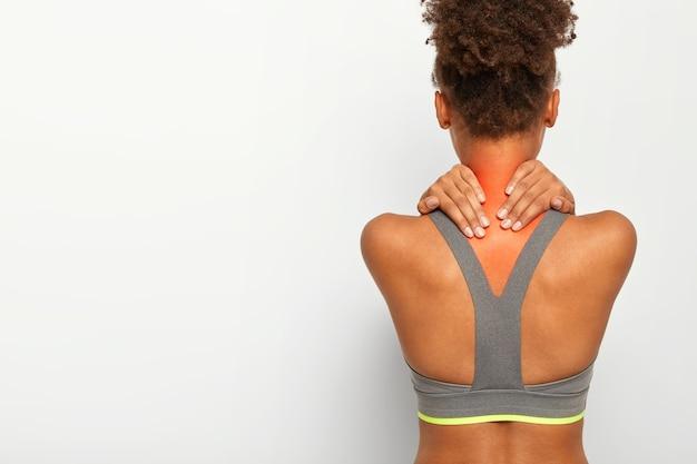 Imagen recortada de una mujer afroamericana sin rostro que toca el cuello con ambas manos, muestra la zona problemática, está lesionada, vestida con ropa deportiva, posa sobre la pared blanca del estudio, espacio en blanco para texto