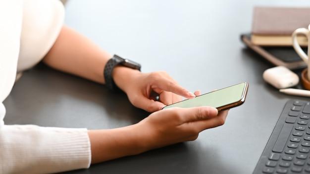 Imagen recortada de mujer creativa trabajando como diseñador gráfico en smartphone.