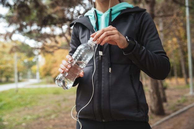 Imagen recortada de una mujer fitness escuchando música con auriculares, sosteniendo una botella de agua mientras está de pie en el parque