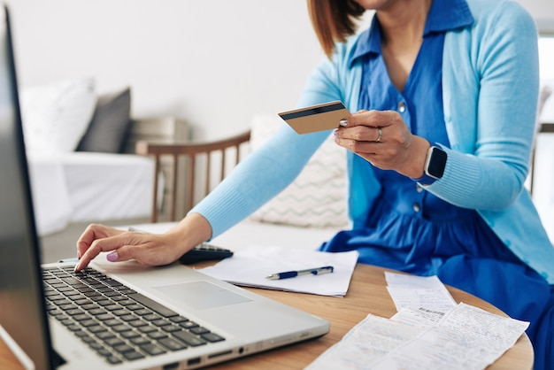 Imagen recortada de mujer ingresando información de su tarjeta de crédito al pagar facturas en línea