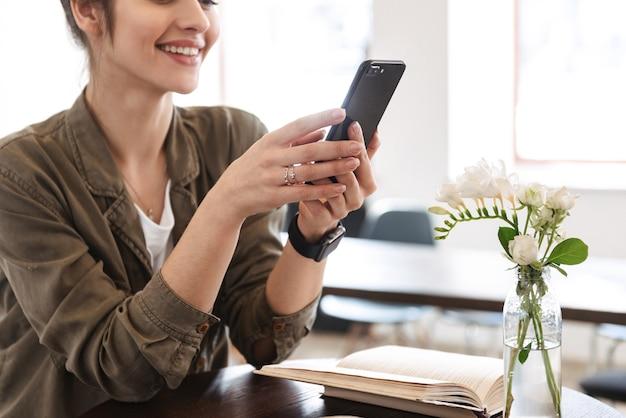 Imagen recortada de una mujer joven y bonita sonriente relajándose en el interior, mediante teléfono móvil