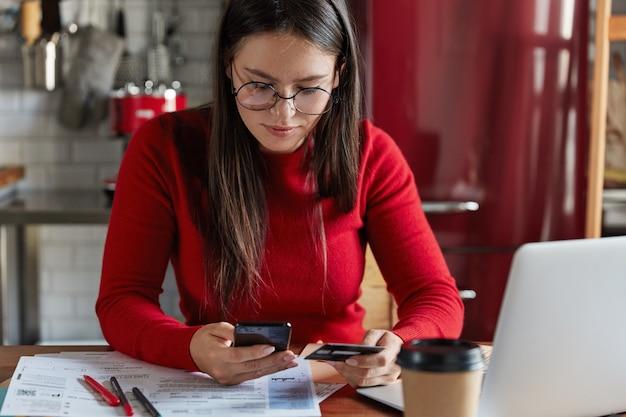 Imagen recortada de mujer morena pecosa en ropa casual roja, tiene un teléfono inteligente moderno y una tarjeta de plástico en las manos