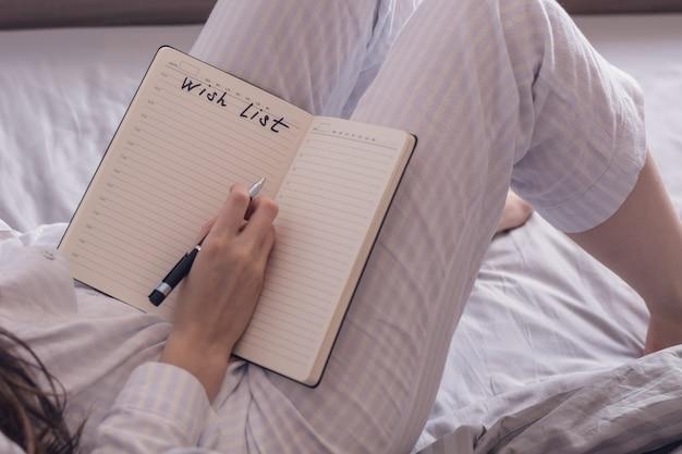 Imagen recortada de una mujer en pijama acostada en la cama y es un deseo