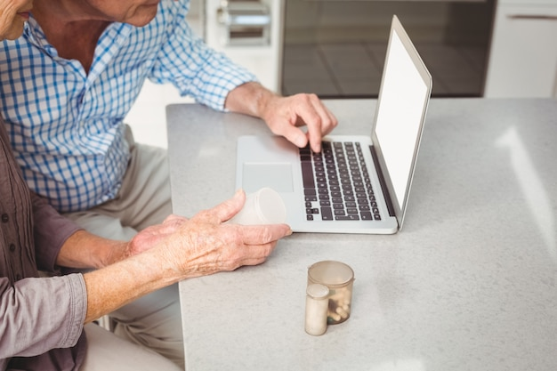 Imagen recortada de pareja senior buscando pastillas en la computadora portátil