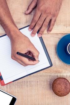 Imagen recortada de la persona que escribe en el diario en la mesa