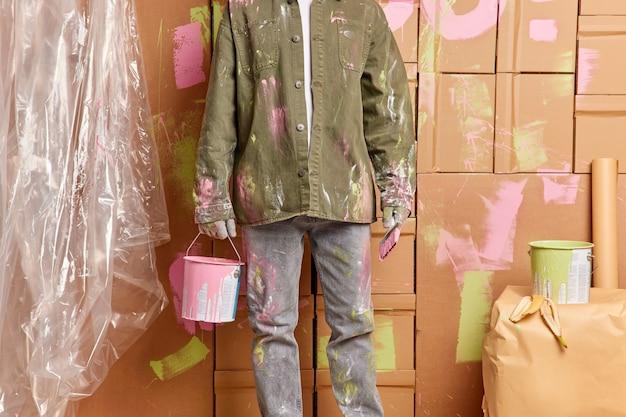 Imagen recortada del pintor hombre sostiene un cubo de pintura rosa y el pincel repara rápidamente los acabados de la casa pintando paredes en la habitación viste camisa informal y jeans concepto de mantenimiento y mejoras para el hogar.