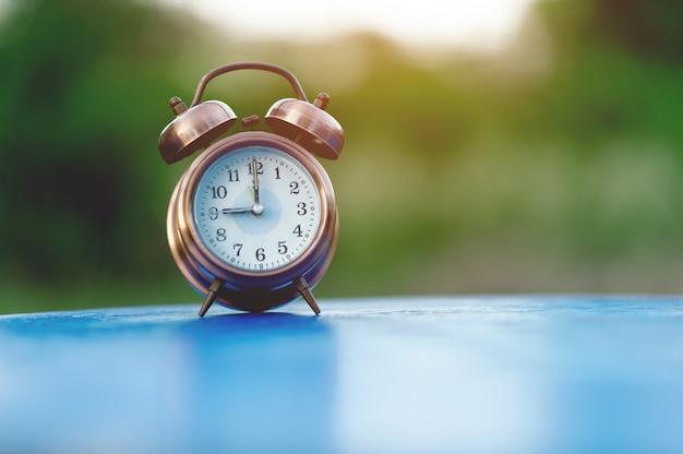Imagen del reloj de alarma dorada colocada sobre una mesa azul.