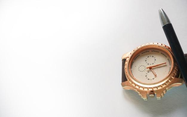 Imagen de reloj y lápiz sobre fondo blanco.