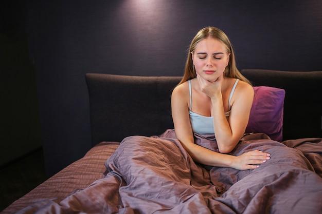 La imagen de la rubia se sienta en la cama y sostiene una mano sobre la garganta. ella tiene dolor allí. la modelo mantiene los ojos cerrados. ella está sola en la habitación.