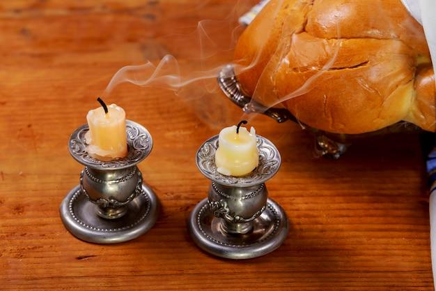 Imagen sabática. candelas de pan challah en mesa de madera