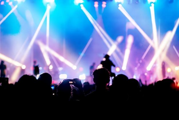 Imagen de la silueta y desenfocada de la iluminación colorida del concierto de entretenimiento en el escenario, audiencia que toma fotos del artista, concierto en vivo borroso y fiesta en la discoteca.