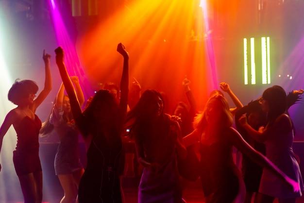 Imagen de silueta de gente bailando en discoteca con música de dj en el escenario