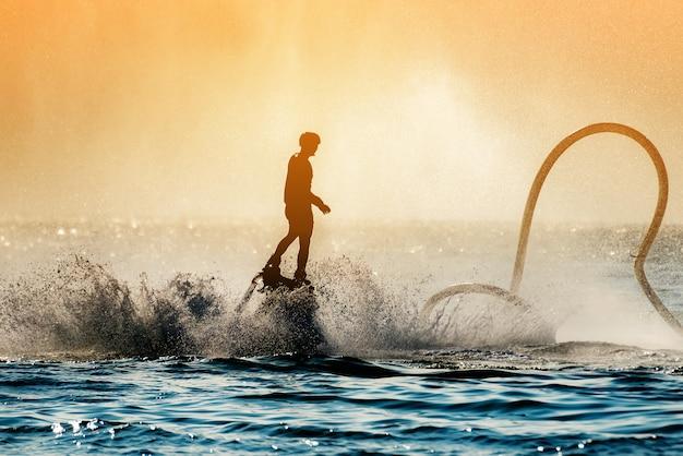 Imagen de la silueta de un hombre mostrando el fly board (aqua board) en el mar, el nuevo deporte espectacular
